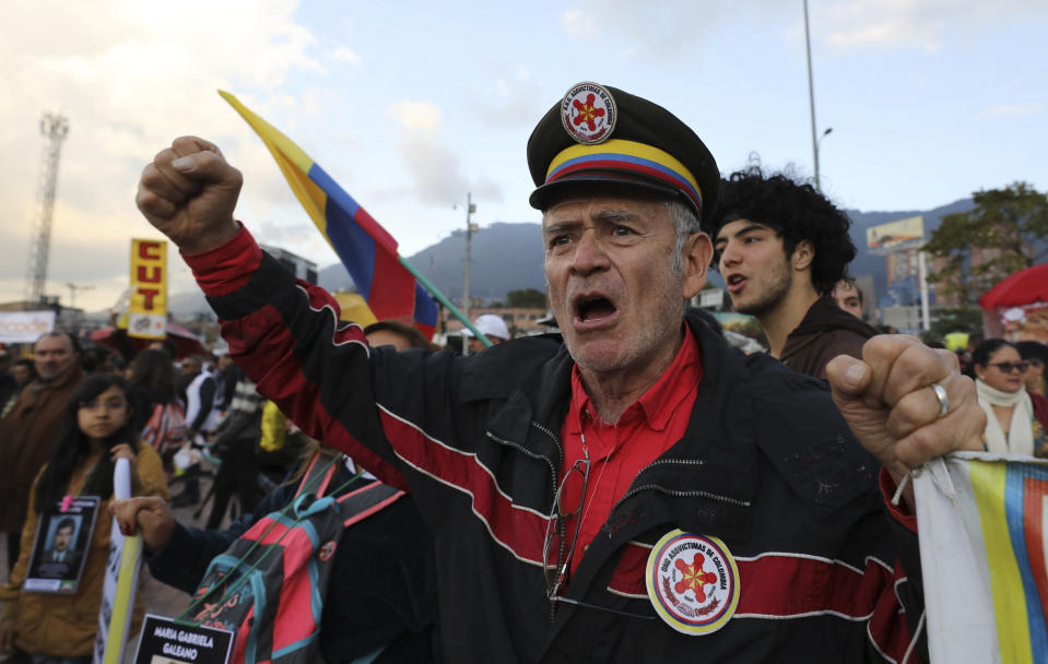 Anti-government protesters rally outside the National Center for Historical Memory, calling for the resignation of its director, Dario Acevedo, on Human Rights Day in Bogota, Colombia, Tuesday, Dec. 10, 2019. As soon as Acevedo was appointed to lead the center, victim organizations called for Colombian President Ivan Duque to reconsider, due to Acevedo's view that the conflict was less a formal struggle against rebels with a cause, than an effort to stamp out criminal and terrorist bands. (AP Photo/Fernando Vergara)