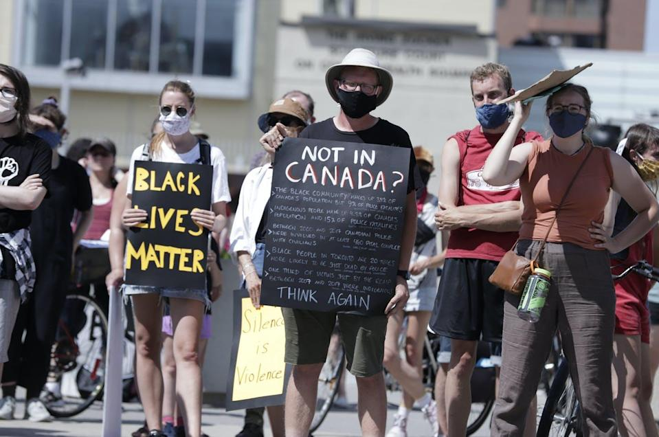 """<span class=""""caption"""">Protesters march and hold up posters along the streets of Hamilton to support anti racism and Black Lives Matter.</span> <span class=""""attribution""""><span class=""""source"""">(Shutterstock)</span></span>"""