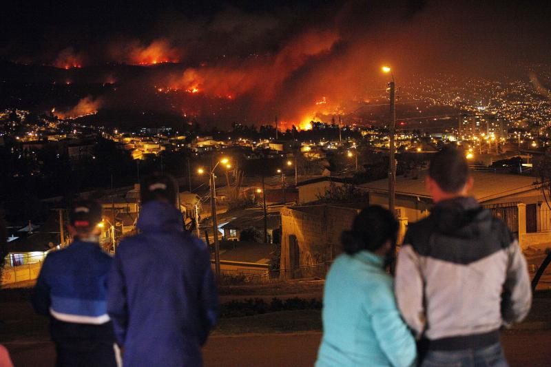 People watch as a forest fire rages towards urban areas in the city of Valparaiso, Chile, Saturday April 13, 2014. Authorities say the first fire has destroyed at least 150 homes and is forcing evacuations. ( AP Photo/ Luis Hidalgo)