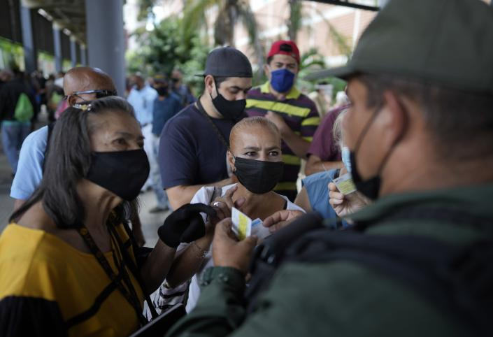 A Bolivarian National Guard checks a residents' vaccination cards as they wait to be injected with a second dose of the Sputnik V COVID-19 vaccine after more than a three-month delay, in Caracas, Venezuela, Tuesday, Sept. 21, 2021. (AP Photo/Ariana Cubillos)
