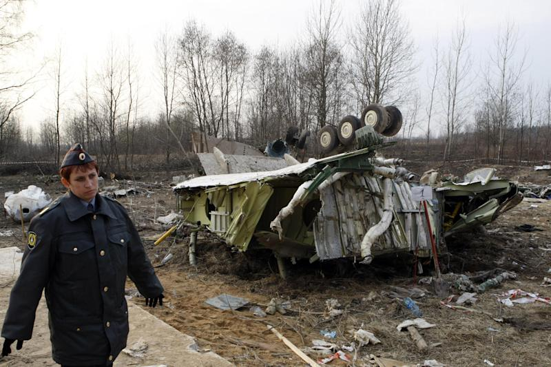 FILE - In this Tuesday, April 13, 2010 file photo, a female policeman secures the site near the wreckage of the Polish presidential plane, that crashed Saturday just outside Smolensk airport, western Russia. Forensic testing has proven that two more victims of the 2010 plane crash in Russia that killed Polish President Lech Kaczynski and 95 others were misidentified and buried in the wrong graves, Polish prosecutors said Wednesday, Nov. 21, 2012, the number of misidentified victims has now grown to six and highlights flaws in the handling of the crash's aftermath in Russia. Such errors are deepening Polish distrust of historic foe Russia, while also fueling Polish conspiracy theories about the cause of the disaster.  (AP Photo/Mikhail Metzel, File)