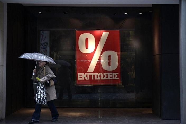 A woman walks past a shop in central Athens on the first day of the winter sales on January 12, 2015 (AFP Photo/Louisa Gouliamaki)