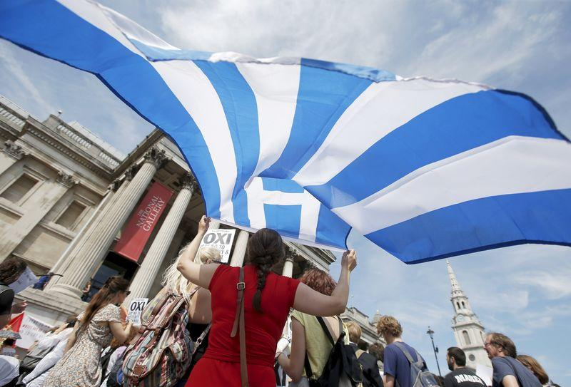 A woman holds the flag of Greece at the 'Greek solidarity festival' in Trafalgar Square, London
