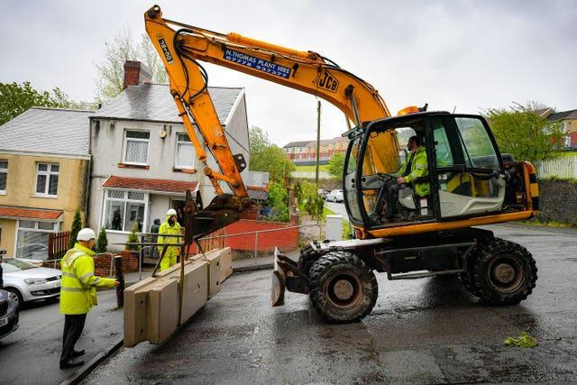Council contractors place heavy concrete barriers at the top of Waun Wen Road, Swansea