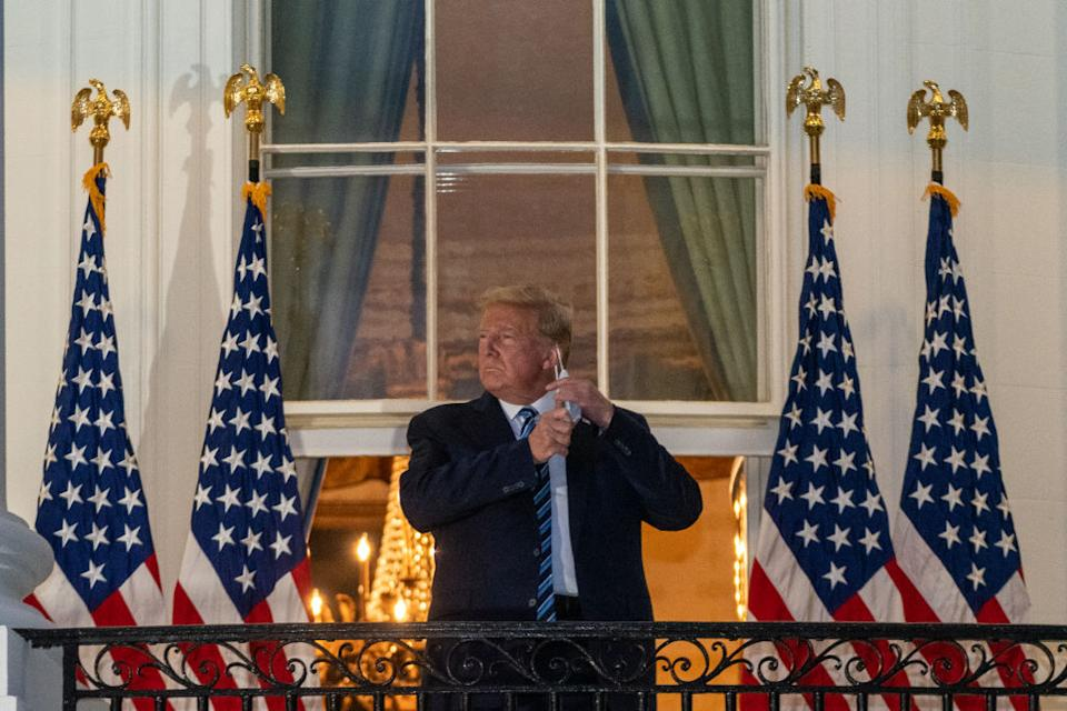 Former President Donald Trump removes his protective mask on the Truman Balcony of the White House in Washington after being discharged from the hospital with Covid-19. Source: Ken Cedeno/Polaris/Bloomberg
