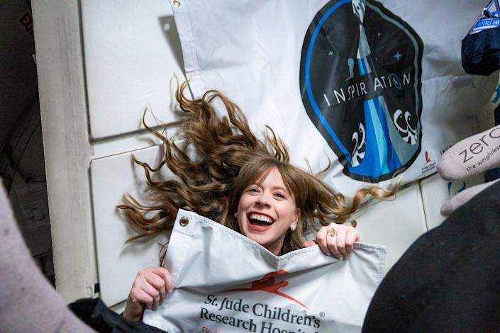 Treated for bone cancer at St. Jude Children's Research Hospital when she was 10, Hayley Arceneaux, now a physician assistant at the famed institution, waves the flag during a zero-gravity training flight. / Credit: Inspi4ration
