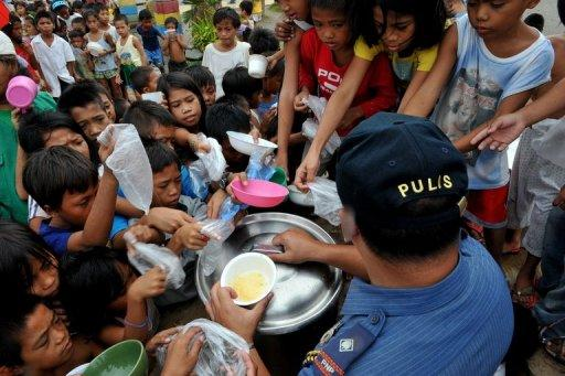 Children queue for rice porridge at a the local government-run feeding centre in the Baseco slum area in Manila. An average of five cups of steamed rice is cooked daily for every Filipino but nine grammes (three tablespoons) of this is wasted