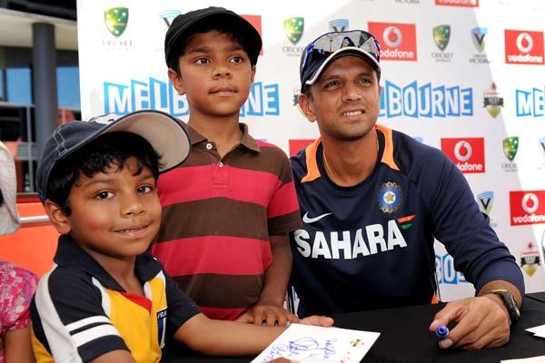 Indian cricket player Rahul Dravid (R) poses with fans as members of the Indian and Australian teams meet the public at an event in Melbourne on December 23, 2011.  Australia and India meet in the first Test match starting 26 December at the Melbourne Cricket Ground (MCG).  AFP PHOTO / WILLIAM WEST