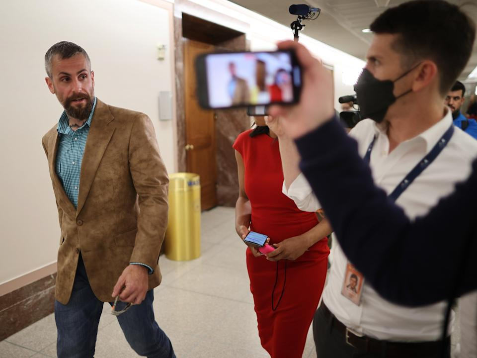 DC Metropolitan Police Officer Michael Fanone (left) is followed by reporters as he heads to a meeting with Sen Susan Collins. (Getty Images)