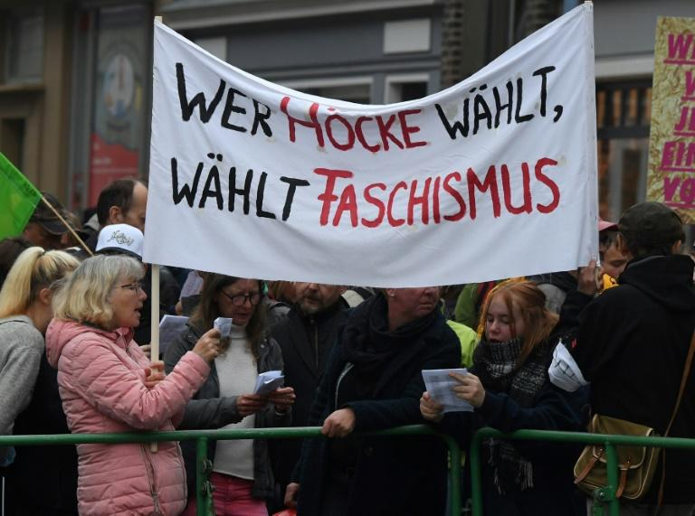 "Anti-AFD demonstrators hold up a banner reading ""Who votes for Hoecke votes for fascism"""