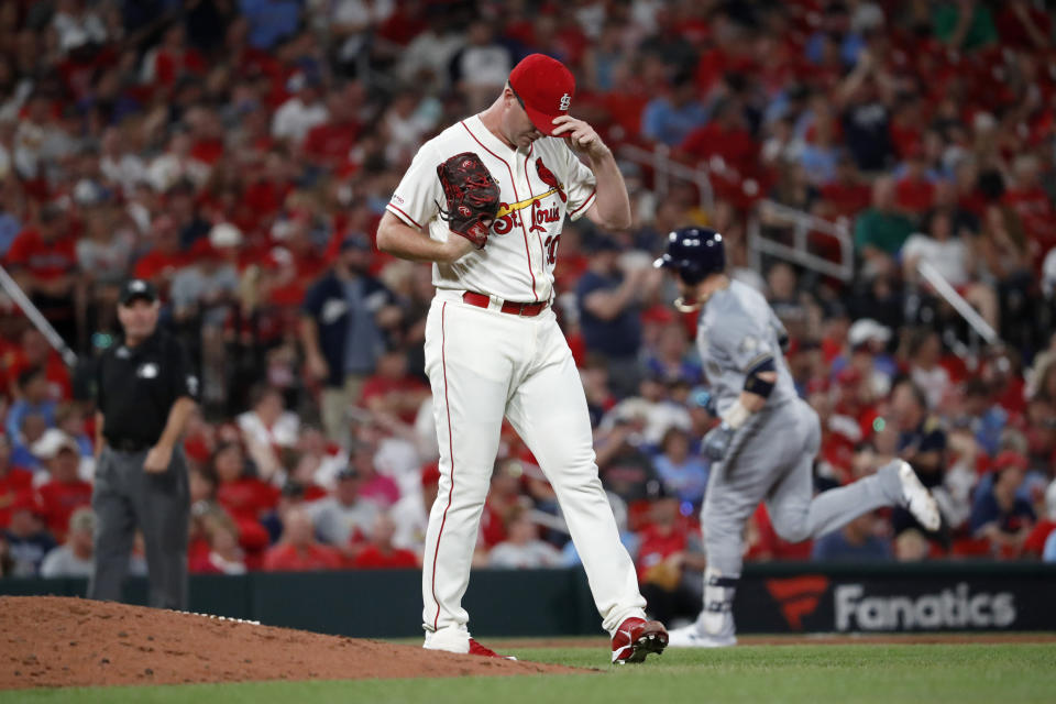 St. Louis Cardinals relief pitcher Tyler Webb, center, adjusts his cap as Milwaukee Brewers' Yasmani Grandal, back right, rounds the bases after hitting a two-run home run during the eighth inning of a baseball game Saturday, Sept. 14, 2019, in St. Louis. (AP Photo/Jeff Roberson)