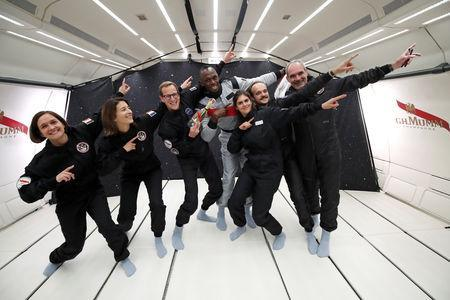 """Retired sprinter Usain Bolt poses with staff members holding a bottle of """"Mumm Grand Cordon Stellar"""" champagne after they enjoy zero gravity conditions during a flight in a specially modified Airbus Zero-G plane above Reims, France, September 12, 2018. REUTERS/Benoit Tessier"""