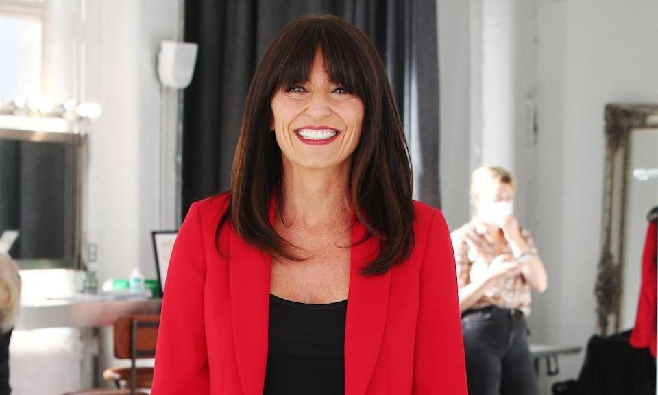 Davina McCall in a red jacket and black top, smiling
