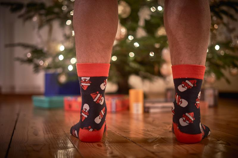 Low Section Of Man Wearing Socks Standing By Christmas Tree On Hardwood Floor