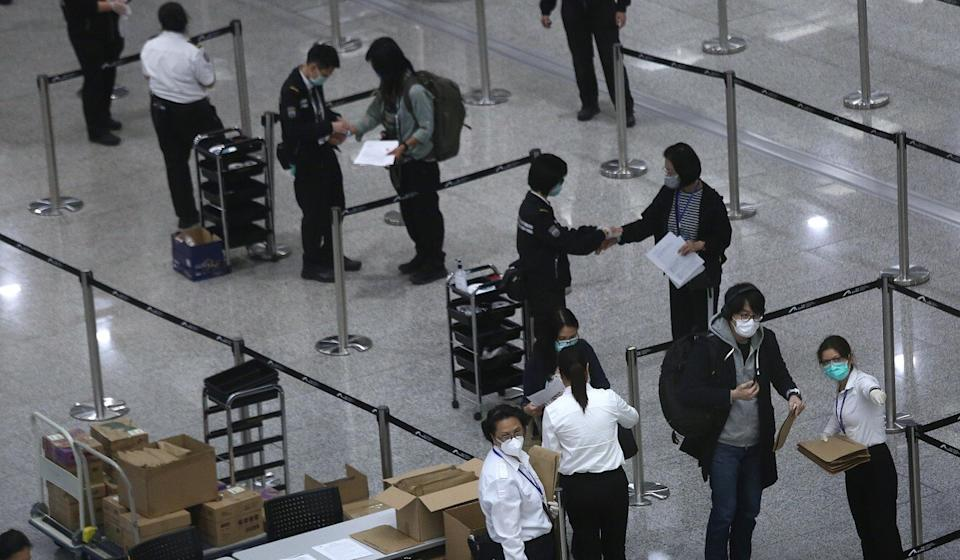 Arrivals receive electronic wristbands at Hong Kong International Airport to monitor their movement during quarantine. Photo: Jonathan Wong