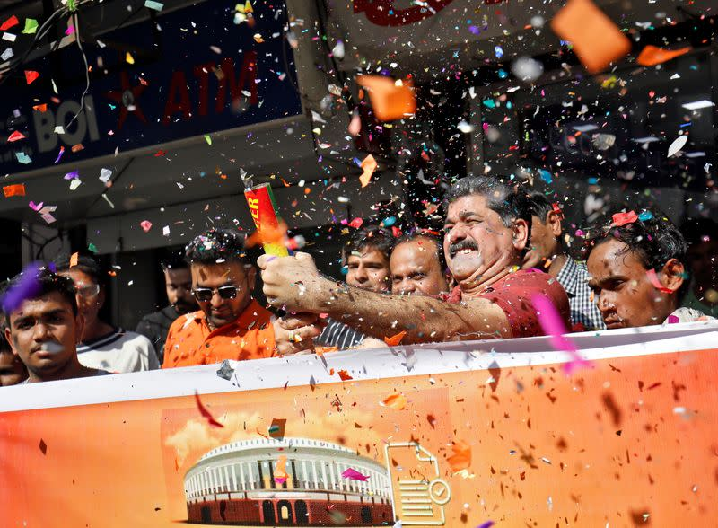 People, who claim to have migrated from Pakistan's Sindh Province, blow confetti to celebrate after India's parliament passed a Citizenship Amendment Bill, in Ahmedabad