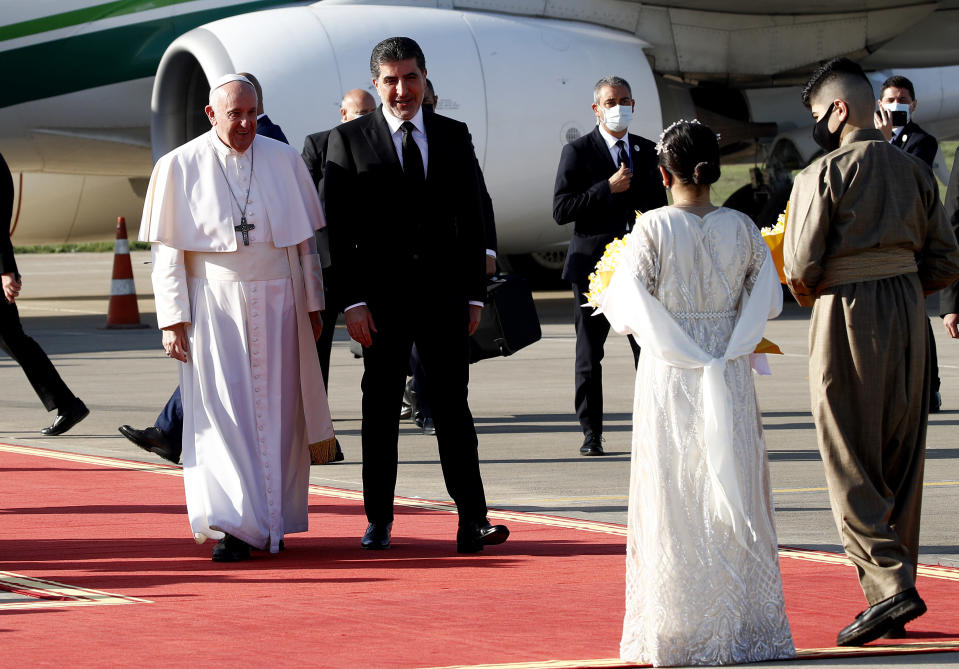 Pope Francis, left, is welcomed by Kurdish President Nechirvan Barzani, second from left , upon his arrival to Irbil airport, Iraq, Sunday, March 7, 2021. Pope Francis arrived in northern Iraq on Sunday, where he planned to pray in the ruins of churches damaged or destroyed by Islamic State extremists and celebrate an open-air Mass on the last day of the first-ever papal visit to the country. (AP Photo/Hadi Mizban)