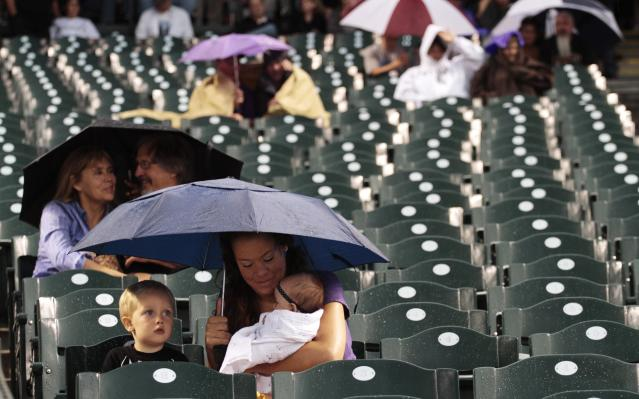 Tawney Summers, of Fort Collins, Colo., holds her 4-month-old daughter, Ema, as they huddle with her son, Maddock, 2, during a rain storm that delayed the Colorado Rockies against the PIttsburgh Pirates baseball game in Denver on Saturday, Aug. 10, 2013. (AP Photo/Joe Mahoney)