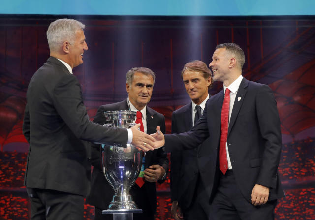 The coaches of Switzerland Vladimir Petkovic, left, Turkey Senol Gunes, second left, Italy Roberto Mancini, second right, and Wales Ryan Giggs who will play in group A, pose with the trophy after the draw for the UEFA Euro 2020 soccer tournament finals in Bucharest, Romania, Saturday, Nov. 30, 2019. (AP Photo/Vadim Ghirda)