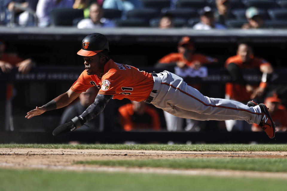 Baltimore Orioles' Cedric Mullins dives home to score a run against the New York Yankees during the seventh inning of a baseball game on Saturday, Sept. 4, 2021, in New York. (AP Photo/Adam Hunger)