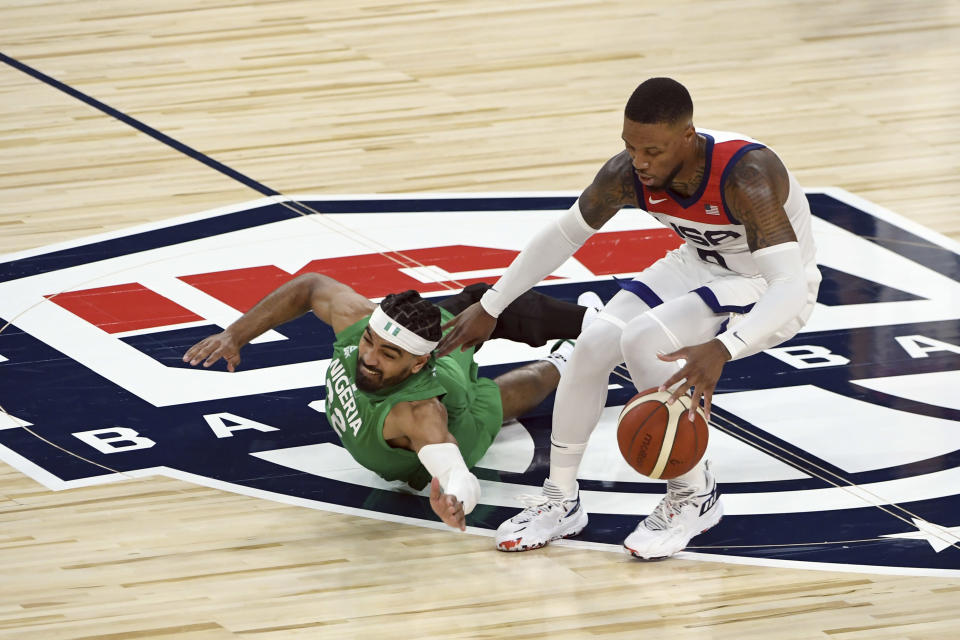 Nigeria's Gabe Nnamdi Vincent (22) and United States' Damian Lillard (6) chase the ball during an exhibition basketball game Saturday, July 10, 2021, in Las Vegas. (AP Photo/David Becker)