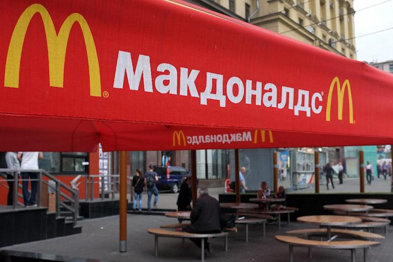 People sit on the terrace of a closed McDonald's restaurant, the first to be opened in the Soviet Union in 1990, in Moscow on August 21, 2014