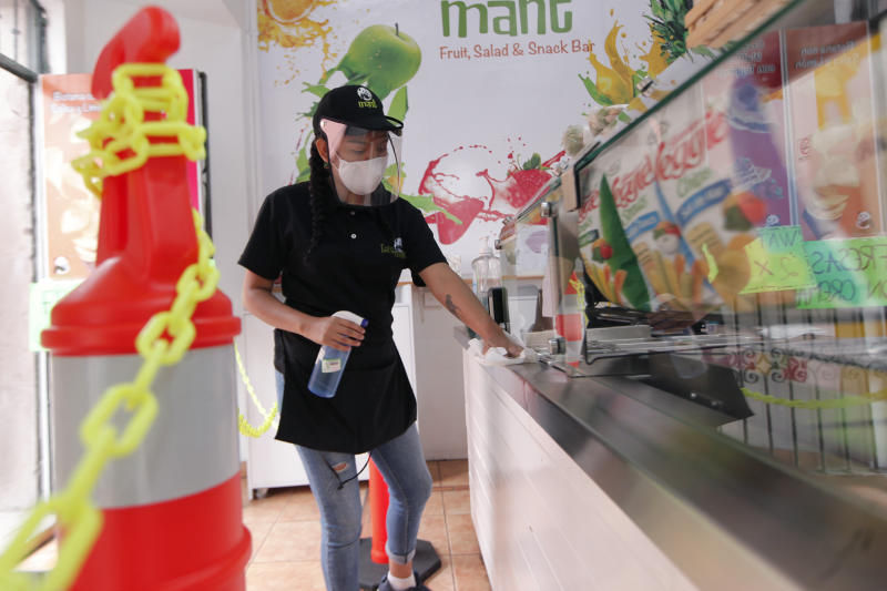 QUERETARO, MEXICO - JUNE 25: A worker cleans a fridge in a ice-cream parlour as Businesses reopen their doors to customers on June 25, 2020 in Queretaro, Mexico. Lockdown restrictions ease as half of the states switch to orange level of alert and the capital amongst other states remain in red alert. (Photo by Cesar Gomez/Jam Media/Getty Images)