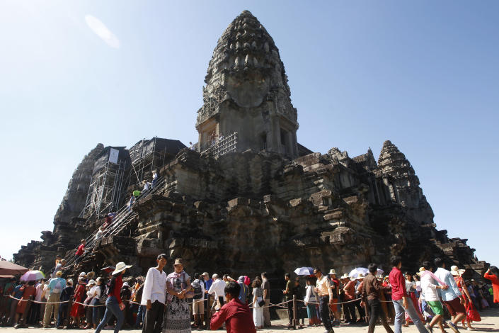 FILE - In this Sunday, Dec. 31, 2017, file photo, tourists line up for stepping up Angkor Wat temple outside Siem Reap, Cambodia. Cambodia is closing the Angkor temple complex to visitors because of a growing COVID-19 outbreak. The temples at Angkor, built between the 9th and 15th centuries, are Cambodia's biggest tourist attraction, though the pandemic has reduced the number of visitors dramatically. The Apsara Authority that oversees the site says the ban on visitors will last until April 20. (AP Photo/Heng Sinith, File)
