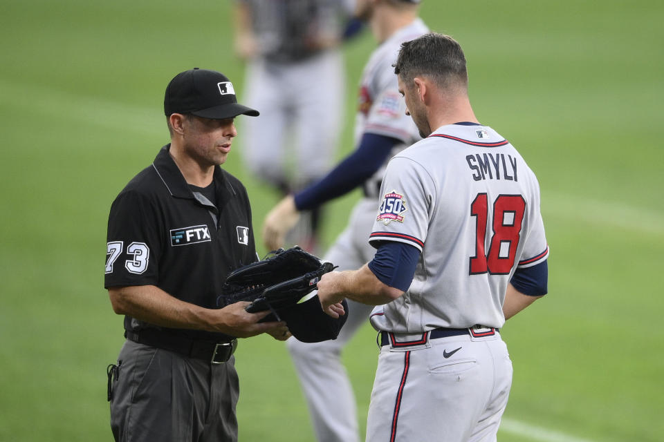 Third base umpire Tripp Gibson (73) inspects the hat and glove of Atlanta Braves starting pitcher Drew Smyly (18) after the first inning of a baseball game against the Baltimore Orioles, Saturday, Aug. 21, 2021, in Baltimore. (AP Photo/Nick Wass)