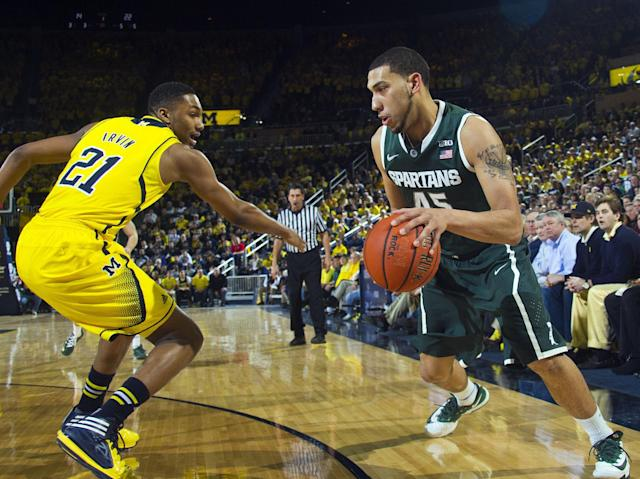 Michigan guard Zak Irvin (21) defends Michigan State guard Denzel Valentine (45) in the first half of an NCAA college basketball game at Crisler Center in Ann Arbor, Mich., Sunday, Feb. 23, 2014. (AP Photo/Tony Ding)