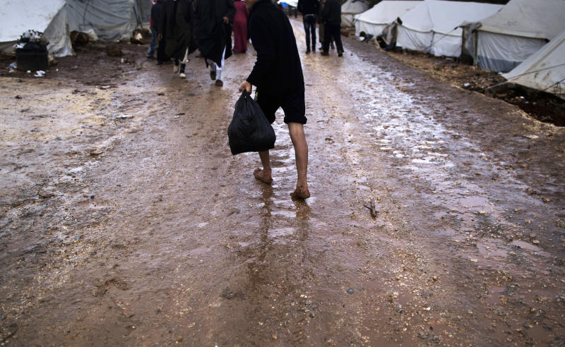 A Syrian boy who fled his home walks barefoot on a muddy path back to his tent, at a camp for displaced Syrians, in the village of Atmeh, Syria, Tuesday, Dec. 11, 2012. This tent camp sheltering some of the hundreds of thousands of Syrians uprooted by the country's brutal civil war has lost the race against winter: the ground under white tents is soaked in mud, rain water seeps into thin mattresses and volunteer doctors routinely run out of medicine for coughing, runny-nosed children. (AP Photo/Muhammed Muheisen)