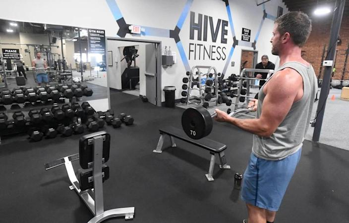 """Devin Bridges curls weights while working out at Hive Fitness in Charlotte on Thursday, July 9, 2020. Gym co-owner Rob Jenkins says any new mask mandates are """"utterly ridiculous"""" at this point."""