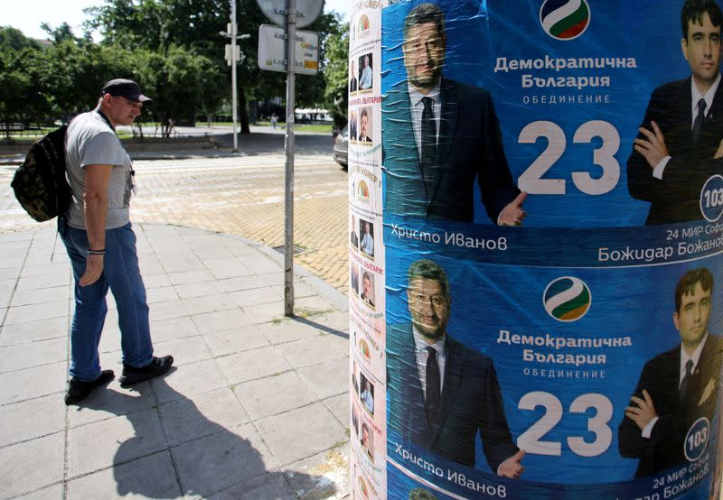FILE PHOTO: FILE PHOTO: Man walks past election posters of Democratic Bulgaria party in Sofia