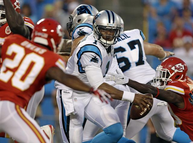 Carolina Panthers' Cam Newton (1) scrambles as Kansas City Chiefs' Chris Owens (20) defends during the first half of an NFL preseason football game in Charlotte, N.C., Sunday, Aug. 17, 2014. (AP Photo/Bob Leverone)
