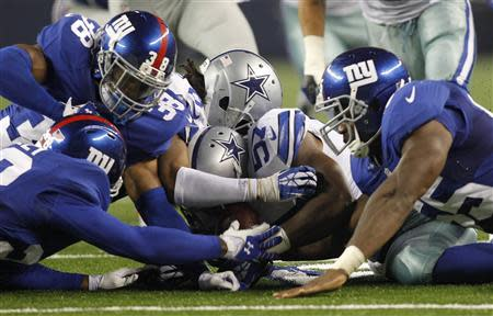 Dallas Cowboys linebacker DeVonte Holloman (57, C) recovers a muffed punt which set up a touchdown for the Cowboys against the New York Giants as corner back Jayron Hosley (L), corner back Trumaine McBride (2nd L) and linebacker Keith Rivers converge on the play in the second half of their NFL football game in Arlington, Texas September 8, 2013. REUTERS/Mike Stone
