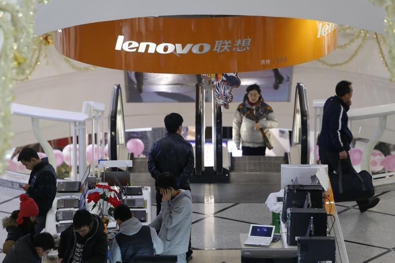 People stand under a sign showing the Lenovo company at a computer market in Shanghai