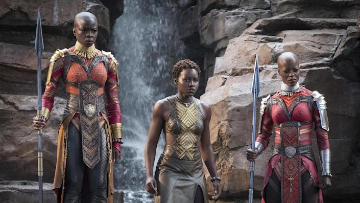 Okoye and another Dora Milaje soldier wield weapons, while Nakai stands between them.
