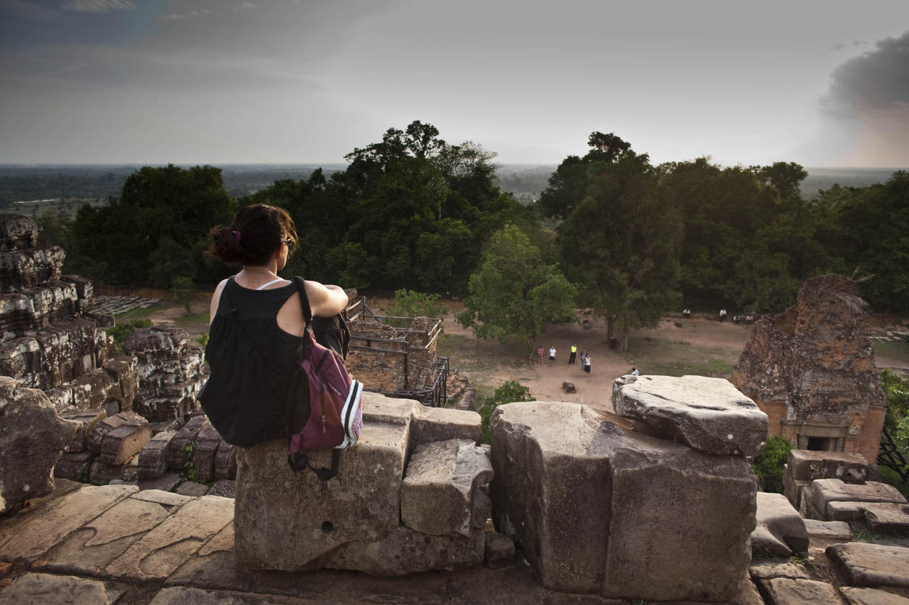 In this photo taken on May 11, 2011, a Western tourist sits on the top of the 10th century temple Bakheng in the Angkor Wat complex near Siem Reap, Cambodia, to view the setting sun. A traffic jam of up to 3,000 tourists surges up a steep hillside, trampling over vulnerable stonework and quaffing beer at a sacred hilltop that provides spectacular sunset views of the massive beehive-like towers rising from the main temple in this ancient city: Angkor Wat. Cambodian Tourism Minister Thong Khon says some 6 million visitors per year are projected by 2020. (AP Photo/David Longstreath)