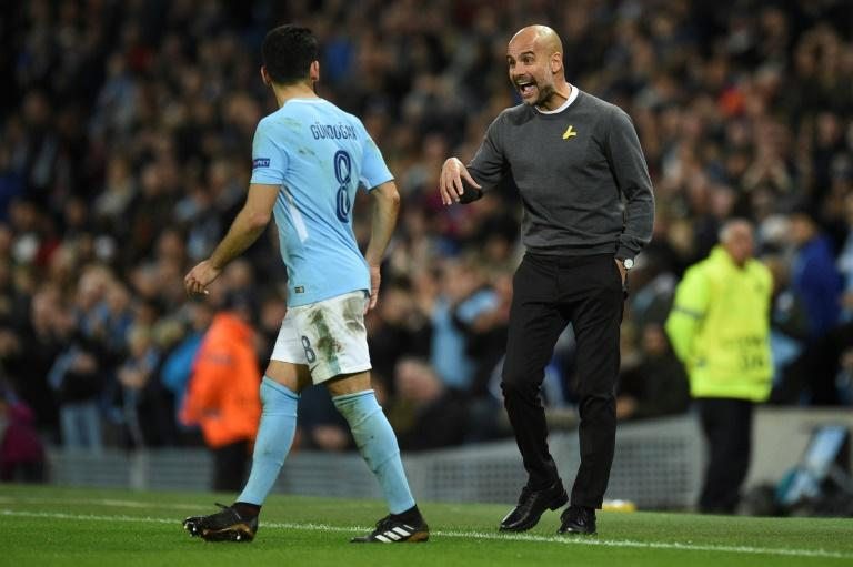 Manchester City's manager Pep Guardiola (R) talks to midfielder Ilkay Gundogan during the UEFA Champions League Group F football match on November 21, 2017