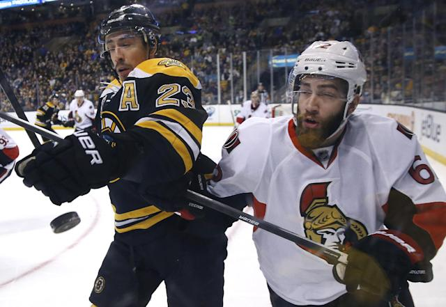 Boston Bruins center Chris Kelly (23) and Ottawa Senators defenseman Eric Gryba (62) compete for the puck along the boards during the second period of an NHL hockey game in Boston, Saturday, Feb. 8, 2014. (AP Photo/Elise Amendola)