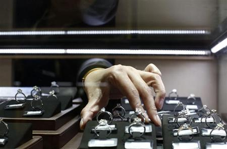 A sales assistant reaches for diamond rings inside a display case at a Tiffany store in Shanghai, September 16, 2013. REUTERS/Aly Song