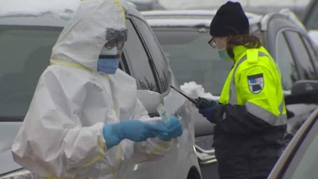 A health-care worker prepares a swab amid a line of vehicles at a drive-thru COVID-19 swab testing site in Mount Pearl on Monday.