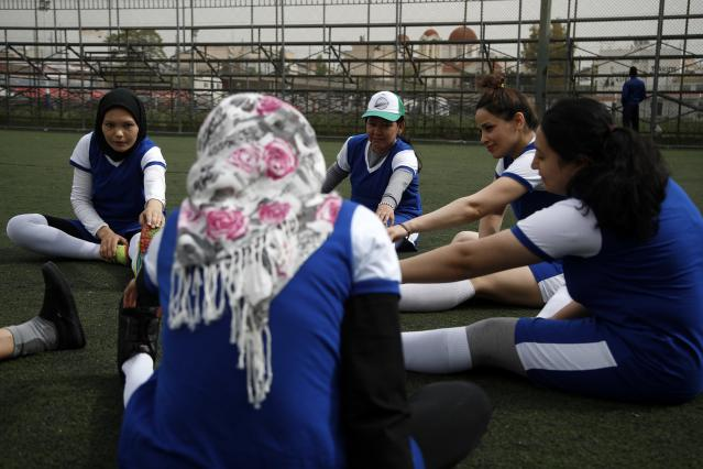 In this Wednesday, April 24, 2019 photo, members of Hestia FC Women's Refugee Soccer team warm up during a training session in Athens. Many of the players at Hestia FC weren't allowed to play or even watch soccer matches in their home countries. Hestia FC was set up by the Olympic Truce Centre, a non-government organization created in 2000 by the International Olympic Committee and Greek Foreign Ministry. (AP Photo/Thanassis Stavrakis)