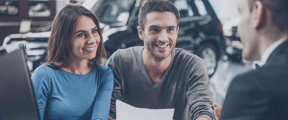 Young couple talking to car salesman at dealership, man is holding papers, everyone smiling