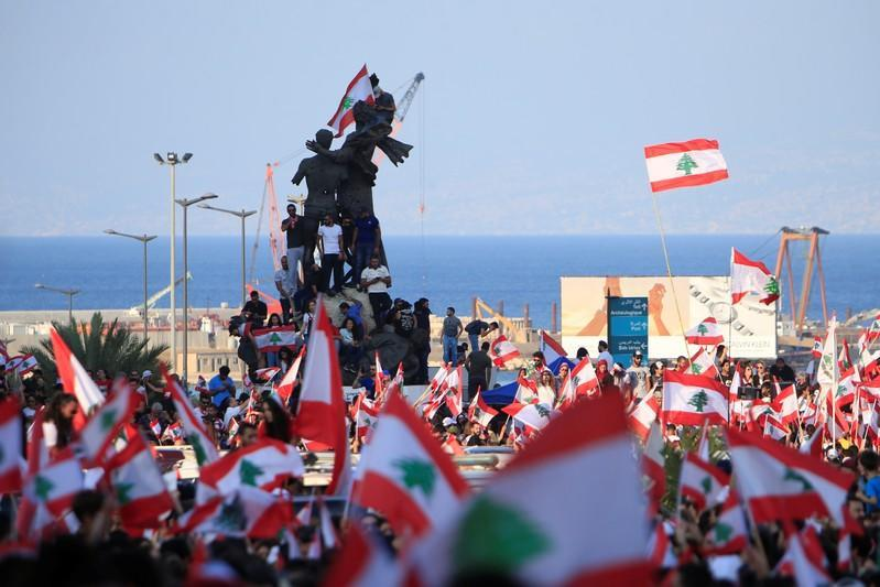 Demonstrators carry national flags during an anti-government protest in Martyrs' Square, downtown Beirut