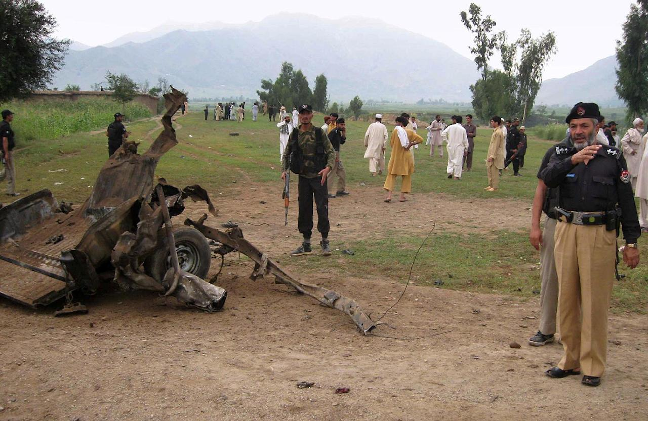 Pakistani police officers stand next to wreckage of a damaged vehicle at the site of a roadside bomb blast that killed at least 15 people and wounded 12 others in northwest Pakistan near the Afghan border in the Jandol area of lower Dir, Pakistan on Sunday, Sept. 16, 2012. Officials said they did not know who set off the bomb, but such attacks are common in the country's remote tribal regions, where militants from both Pakistan and neighboring Afghanistan are active. (AP Photo/Rohullah Shakir)