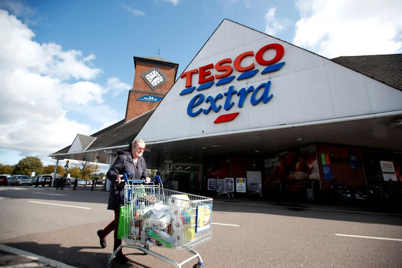 FILE PHOTO: A woman pushes a shopping cart as she walks past a Tesco supermarket in Hatfield