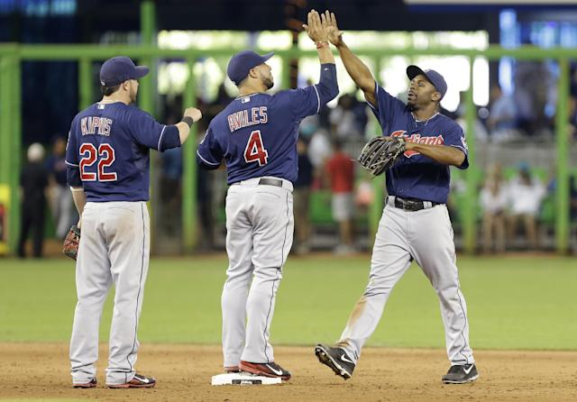 Cleveland Indians center fielder Michael Bourn, right, celebrates with shortstop Mike Aviles (4) and second baseman Jason Kipnis (22) after the Indians defeated the Marlins 2-0 during an interleague baseball game, Sunday, Aug. 4, 2013, in Miami. (AP Photo/Lynne Sladky)