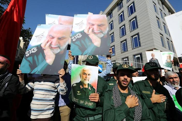 Iranian men, including members of the Iranian revolutionary guard, hold portraits during the funeral procession of Iran's Revolutionary Guards Brigadier General Hossein Hamedani in Tehran on October 11, 2015 (AFP Photo/Atta Kenare)