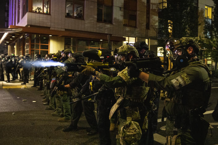 Federal police try to take control of the streets during protests on Friday in Portland, Ore. (Paula Bronstein/AP)